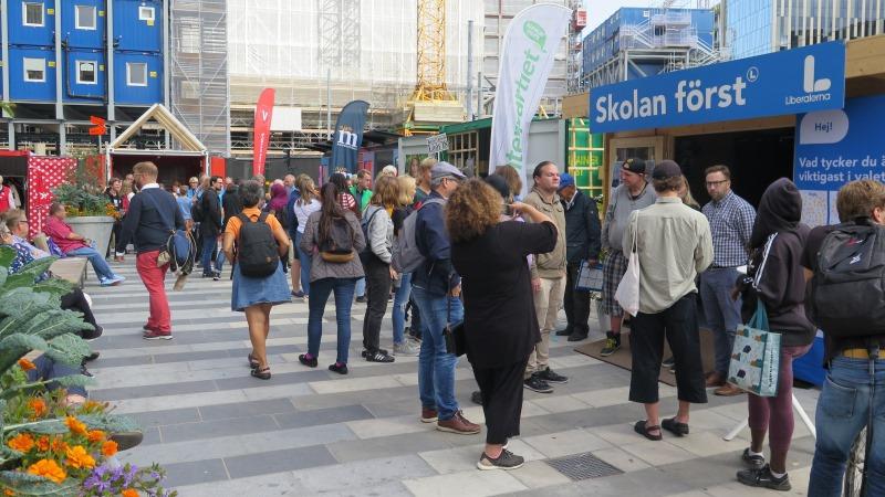 Valstugor på rad på Sergels torg. Besökare står och lyssnar framför Liberalernas stuga i förgrunden.