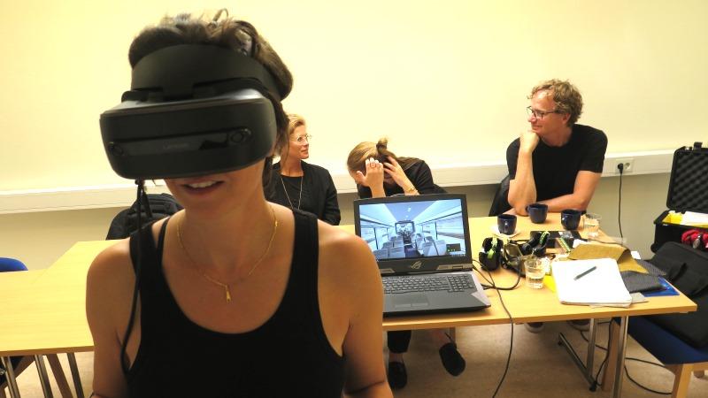 I förgrunden en kvinna med svarta vr-glasögon, som ser ut som en liten låda som täcker halva ansiktet. I bakgrunden en dataskärm som visar interiör i en tågvagn.