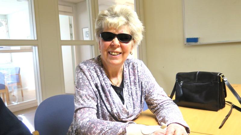 En kvinna med ljust hår, solglasögon och en lila blus.