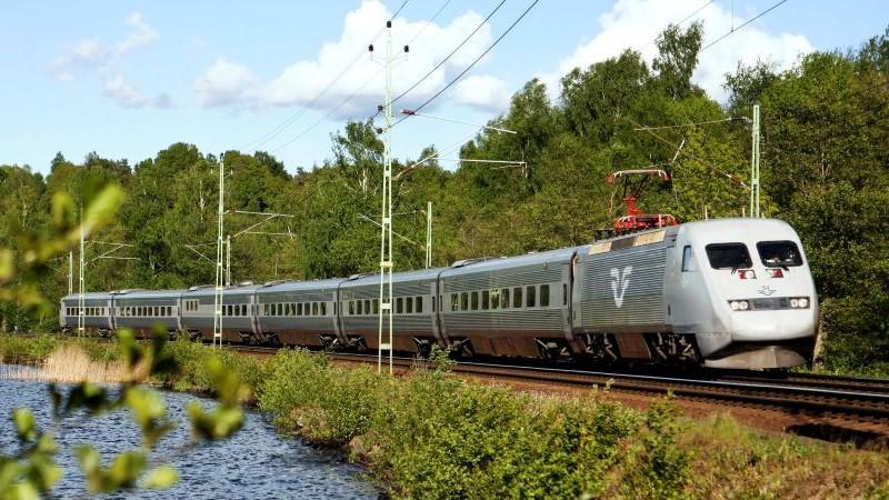Ett tåg far från bakre vänster del av bilden till höger närmare kameran. Det reser genom ett grönskande landskap med en sjö till vänster.