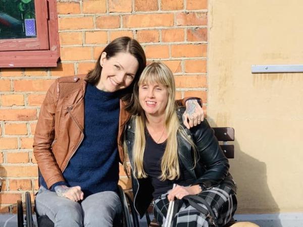 Kvinna med ljust hår och vit käpp sitter bredvid brunhårig kvinna i rullstol vid en husvägg