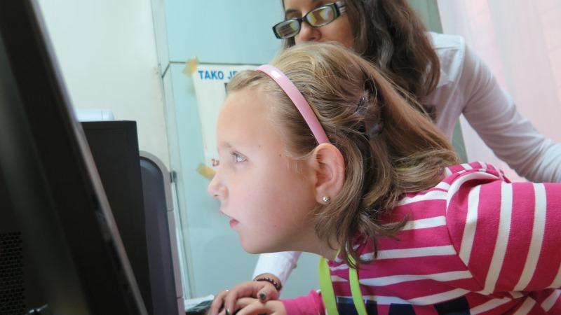 Flicka med halvlångt blont hår och rödvitrandig tröja med ansiktet nära en datorskärm. I bakgrunden en vuxen som håller hennes hand och tittar över hennes axel.