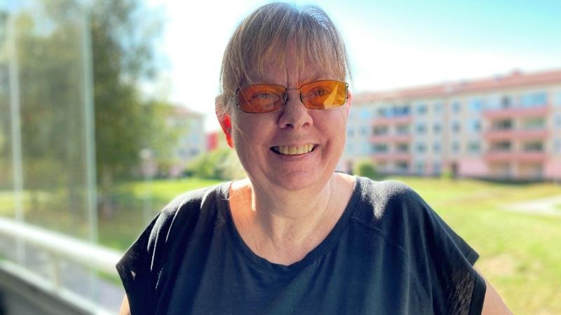 Leende kvinna i glasögon och tofs står på sin balkong
