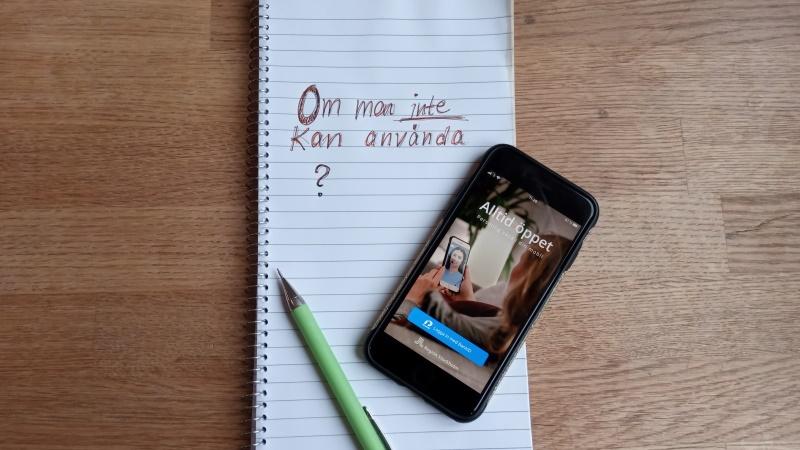 På träbord ligger vitt block, grön penna och mobiltelefon. Appen Alltid Öppet syns i displayen