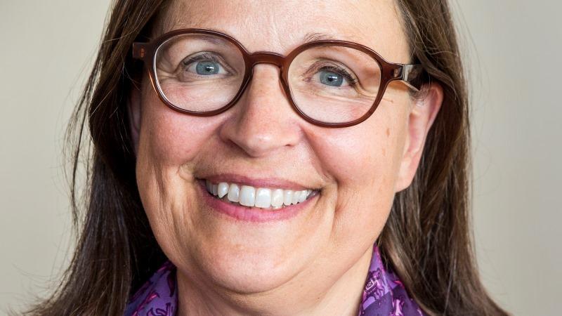 Medelålders kvinna med runda glasögon och brunt hår.