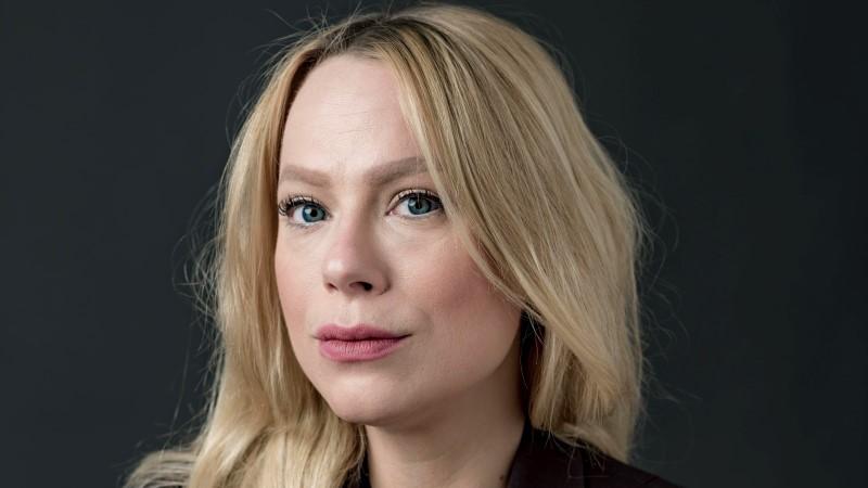 Ansikte på blond ung kvinna, långt hår. Brun fondvägg