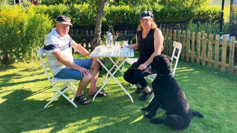 Kvinna och man sitter vid bord i en solig sommar trädgård