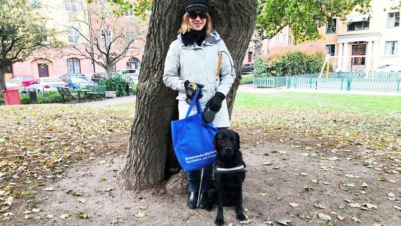 Kvinna står vid träd i park med ledarhund, svart labrador