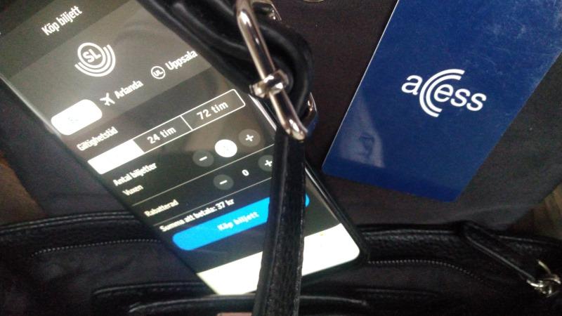 En smart telefon med SL-appens biljettfunktion öppen sticker upp ur en handväska intill ett mörkblått SL-kort med texten Acess.