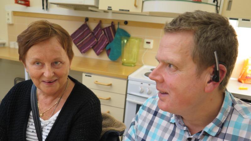 En man som sitter med hörsnäcka och en kvinna som ler.