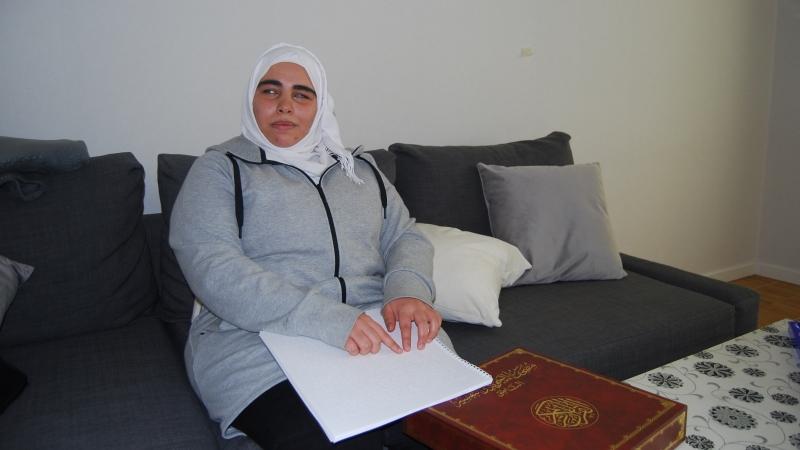 Kvinna med vit slöja och grå tröja sitter i soffa och läser punkt