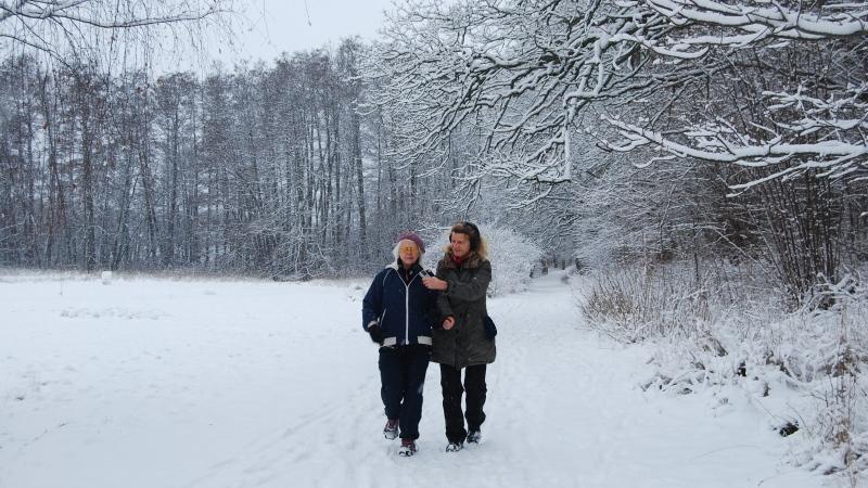Landskap i snö. Två kvinnor springer bredvid varandra.