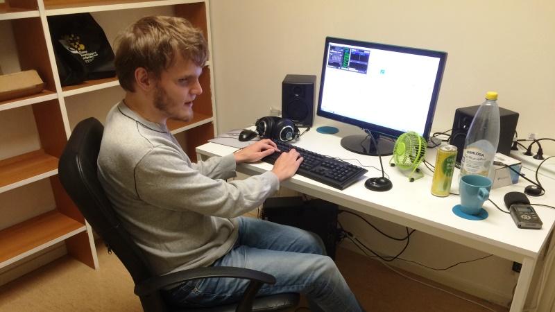 Philip är ung, blond med skägg och klädd i grå tröja och jeans. Han sitter framför en dator.