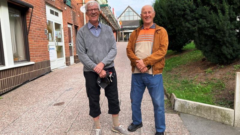Två äldre leende män står på gata vid köpcentrum.
