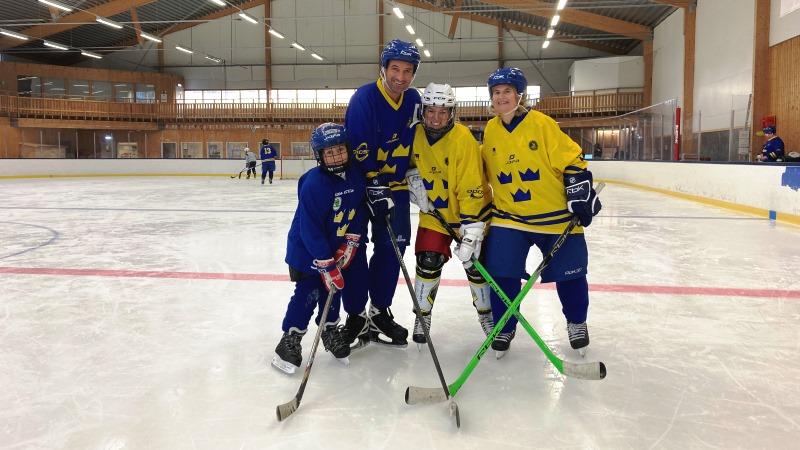 Tre vuxna och ett barn i ishockeymundering med klubbor på isrink.