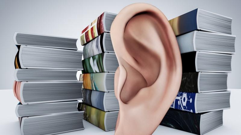 Tecknad bild på stort frilagt öra framför tre högar av böcker.