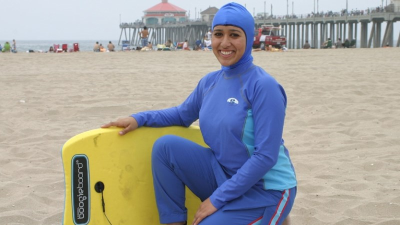 Kvinna i blå burkini på strand.