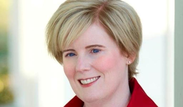Kvinna med ganska kort blont hår och snedlugg. Man skymtar en röd krage.