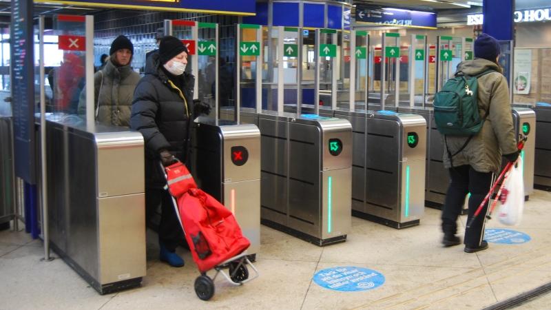 Tunnelbana,spärrar, dam med röd shoppingväska.