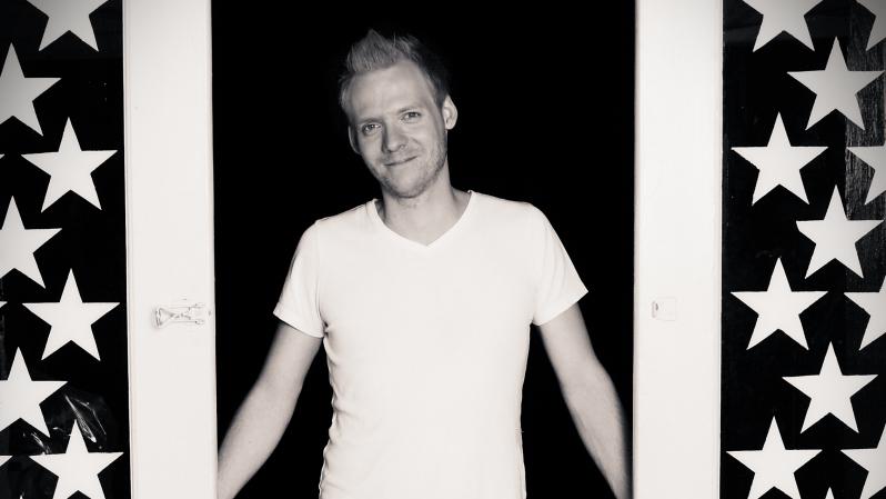 Johan Häglerud står i en dörröppning. Han har en vit t-shirt och håller armarna diagonalt utåt.