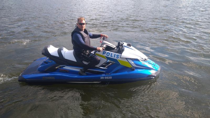Polis i flytväst och mörka solglasögon sitter på en vattenskoter omgiven av vatten.