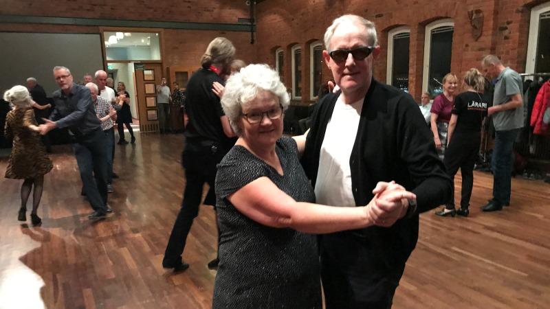 Ett dansande äldre par i en danssal med parkettgolv och andra par i bakgrunden. Han har svart kofta och vit T-tröja, hon en svart klänning.