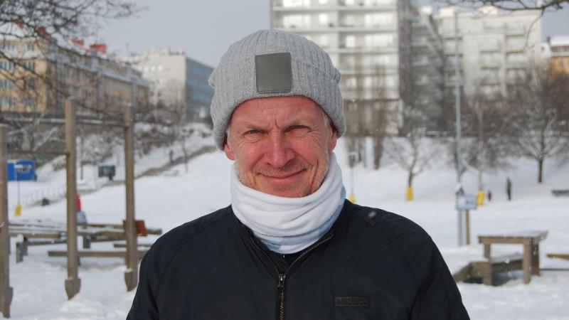 Man i snöigt landskap. Grå, stickad mössa, vit halsduk.