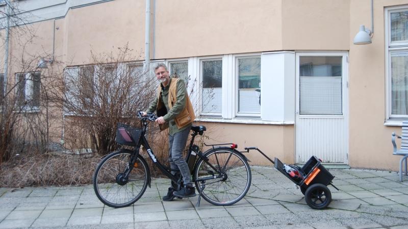 Gråhårig man på cykel med liten kärra bak, han har gul väst, grön tröja. Buskar, hus i bakgrund.