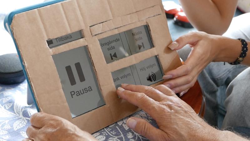 Flera händer håller i en prototyp av en läsplatta i pappkarton