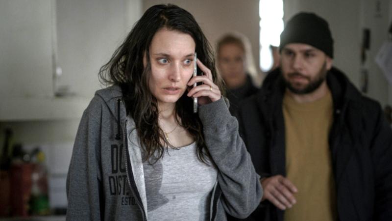 Kvinna talar i mobilen, har långt brunt hår, grå kofta, T-shirt med fläck, läckande bröstmjölk. Oro i blick.