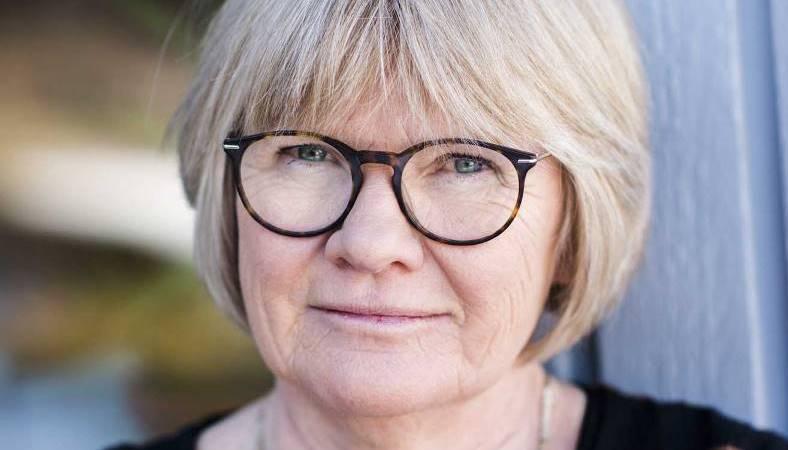Närbild på Elisabeth Wallenius. Hon har blå ögon, en gråblond page med lugg, rundade brundmelerade glasögon. Brun och svartrandig tröja.