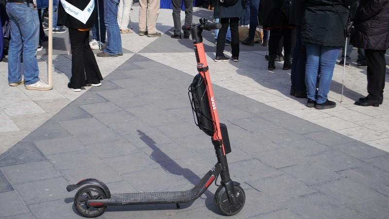 Ensam elsparkcykel på Sergels torg. En smal bräda med hjul fram och bak och ett midjehögt styre längst fram.