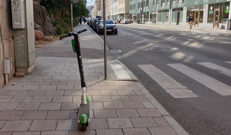 Elsparkcykel står på en trottoar i stad