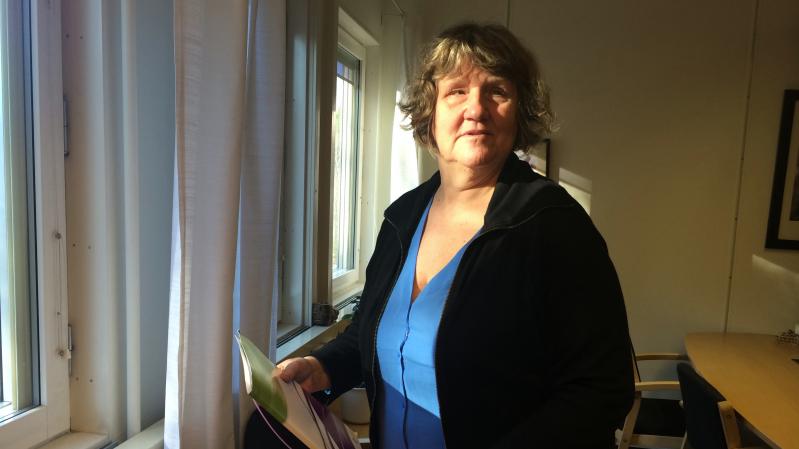 Eva har en blå tröja och en svart kofta. Hon står vid ett fönster med sol i ansiktet.
