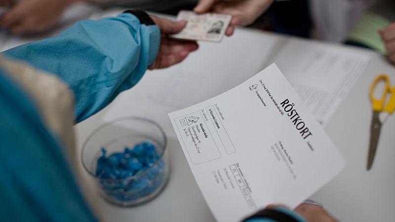 Närbild på hur en person med ett röstkort i högra handen sträcker fram id-kort med vänster hand. Förutom händer och armar syns inget av personen, som är klädd i en blå jacka.