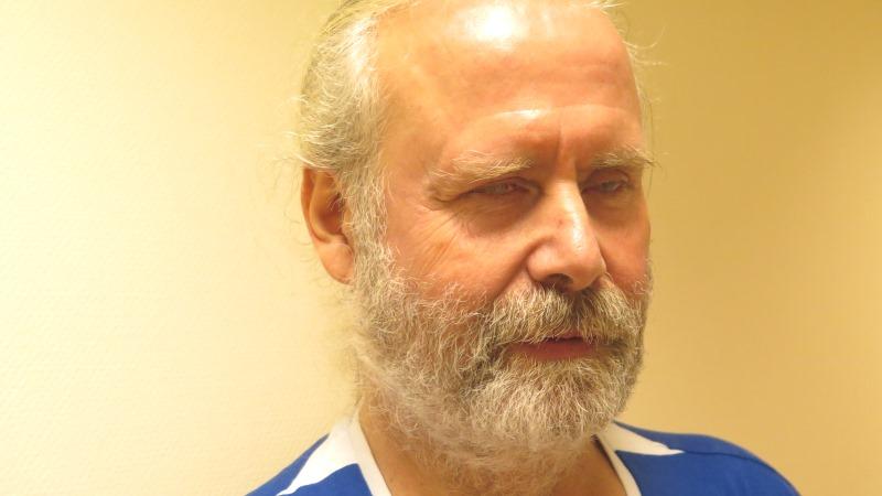 Fredrik Ahlkvist har gråvitt hår och skägg. Håret är samlat i en hästsvans och han har en båvitrandig tröja.