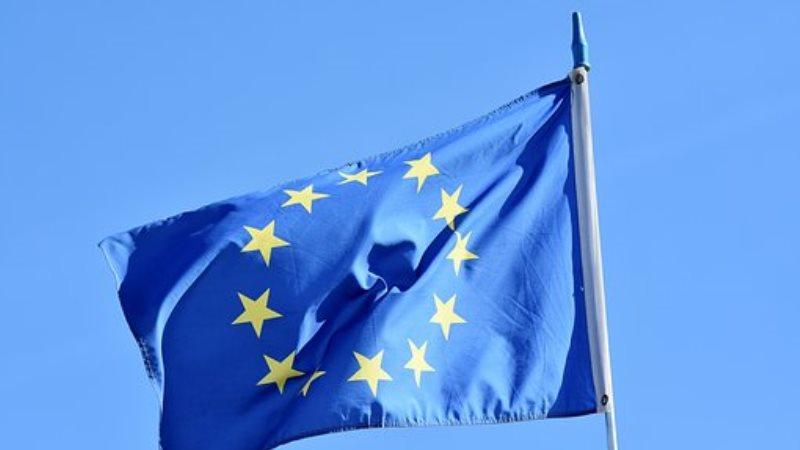 Närbild på EU.s blå flagga, med en stor cirkel av små gula stjärnor, som vajar i vinden mot en ljusare blå himmel.