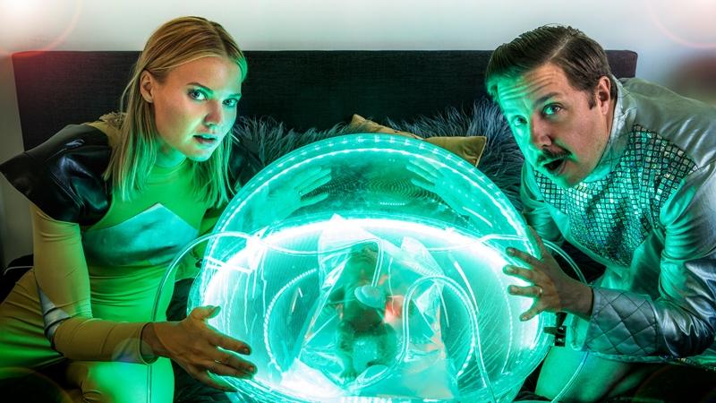 En man och kvinna i framtidsdräkter med stor glasglob mellan sig, i ligger ett ofött barn.
