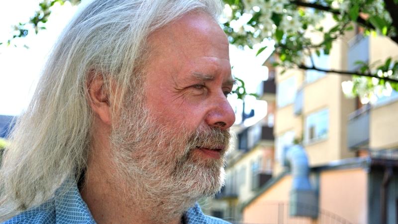 Fredrik Ahlkvist tittar bort från kameran. Han har gråvitt axellångt hår och skäggstubb.