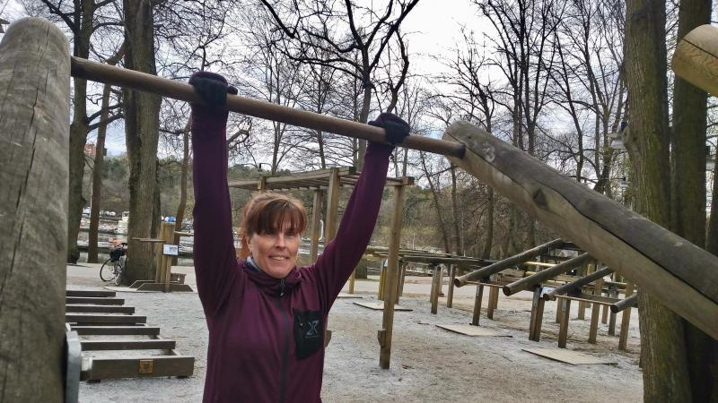 Kvinna i lila träningströja på utegym