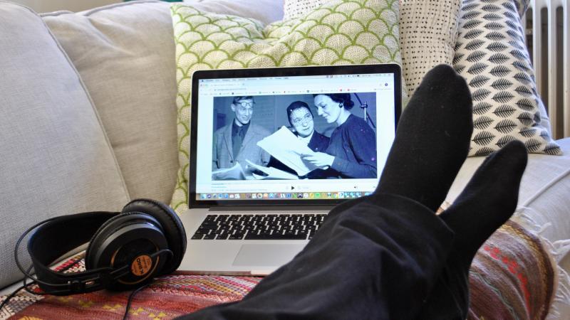 bild på underben, någon ligger i soffa tittar på en laptop med en svartvit film.