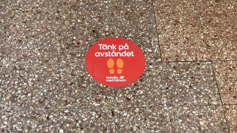 Rött stort klistermärke på stengolv i affär, med text, tänk på avståndet, handla med hänsyn
