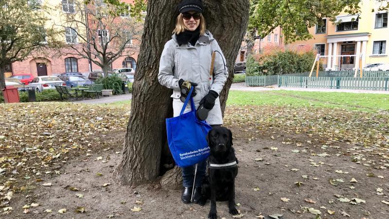 Kvinna står vid ett stort träd i park, svart ledarhund bredvid