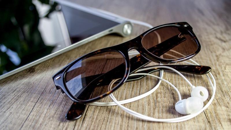 Ett par bruntonade solglasögon ligger på en sladd till hörlurar och man skymtar en läsplatta.