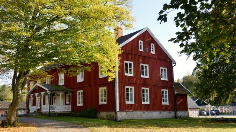 Glimåkra folkhögskola. En stor röd byggnad med vita knutar i lantlig lummig miljö.