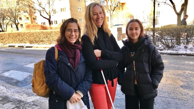 Tre kvinnor i halbild, en har vit käpp.