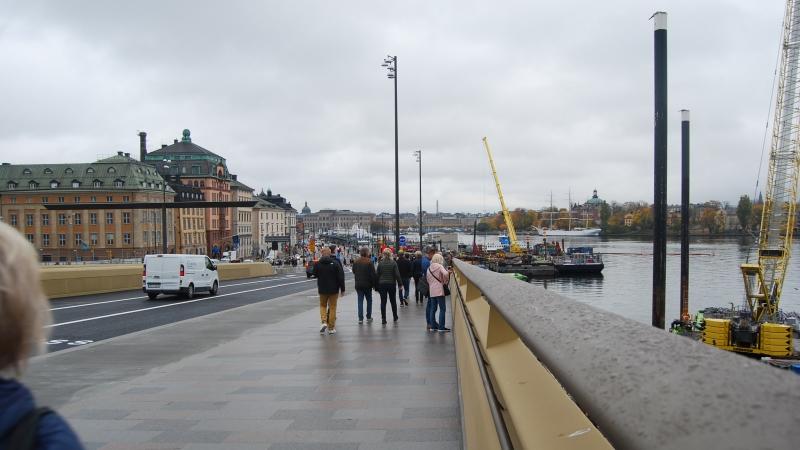 Gående människor och bilar på bron i riktning mot Gamla stan, inramade av de guldkantade räckena i varm, lätt skimrande guldfärg.
