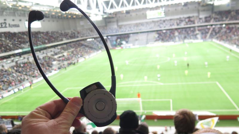 Syntolkningsmottagare med hörlurar, fotbollsplan i bakgrunden