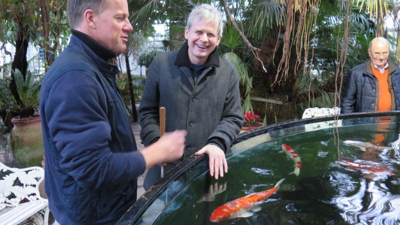 Två män vid bassäng med simmande fiskar.