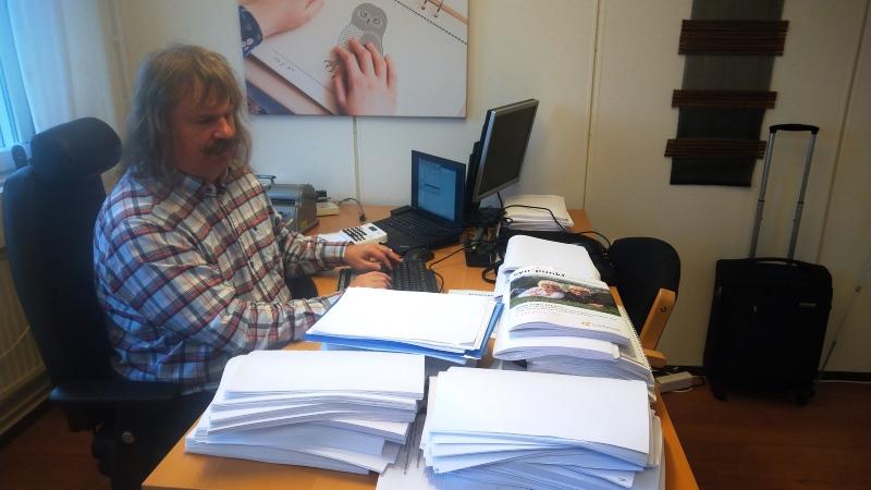 En man med yvig mustasch och gråsprängt axellångt hår klädd i rutig skjorta sitter vid ett skrivbord belamrat med högar av punktskriftsdokumentent.
